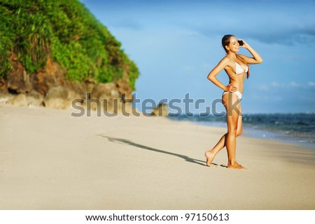 young beautiful woman on the beach with cell phone - stock photo