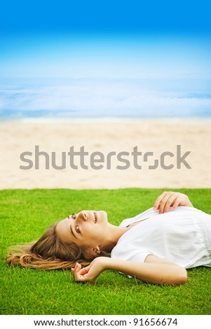 Young beautiful woman on the green grass