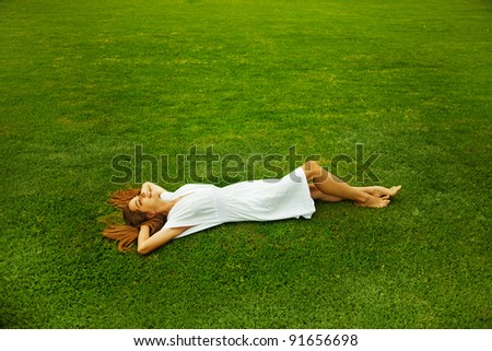 Young beautiful woman  on the green grass - stock photo