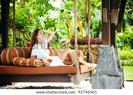 Young beautiful woman on the outdoors bed in balinese resort - stock photo