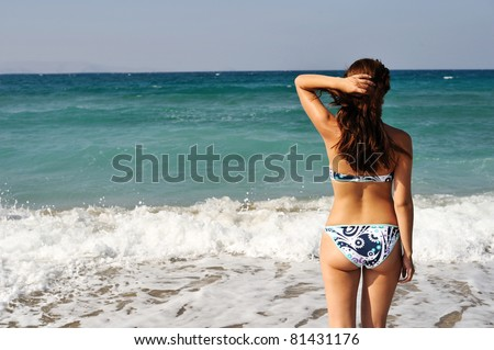 Young beautiful woman on the sunny  beach in bikini - stock photo