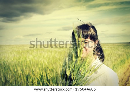 Young beautiful woman on wheat field - stock photo