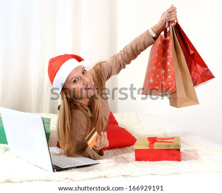 Young beautiful woman online Christmas shopping with computer and credit card   - stock photo