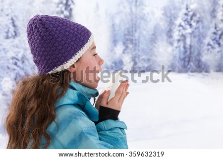 Young beautiful woman outdoor blowing nose in winter