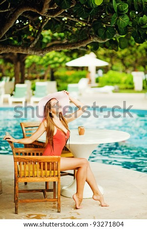 Young beautiful woman outdoors sitting on the chair near swimming-pool