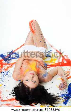 Young beautiful woman painted in number of colors laying on white floor - stock photo