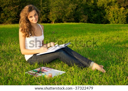 Young beautiful woman painting on a green meadow