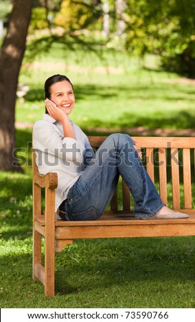 Young beautiful woman phoning on the bench - stock photo