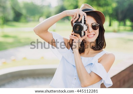 Young beautiful woman photographer taking images with camera - stock photo