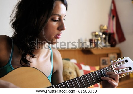 Young beautiful woman playing guitar in her room.