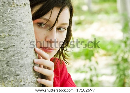 Young beautiful woman playing hide and seek in the trees. - stock photo