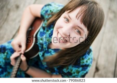 Young beautiful woman playing music outdoors - stock photo