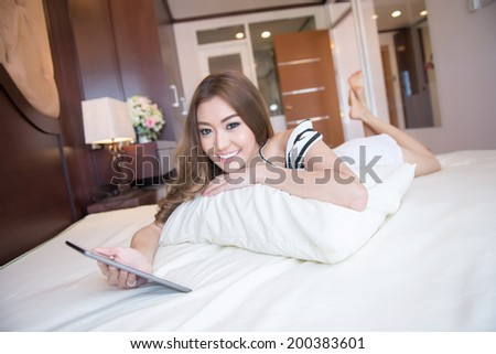 Young beautiful woman playing tablet - stock photo