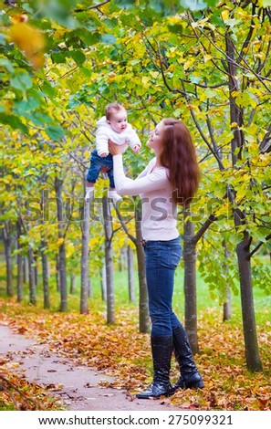 Young beautiful woman playing with her baby in a park. Mother and child outdoors in fall. Parent and kid walking in autumn forest. - stock photo
