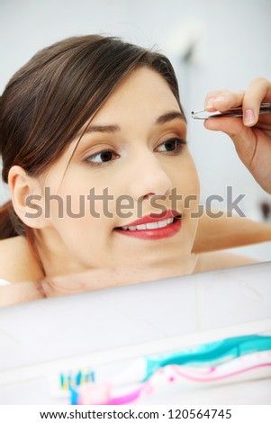 Young beautiful woman plucking her eyebrows with tweezers at her bathroom
