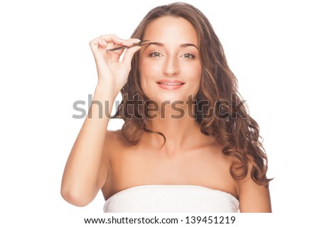 Young beautiful woman plucking her eyebrows with tweezers. Isolated on white background - stock photo