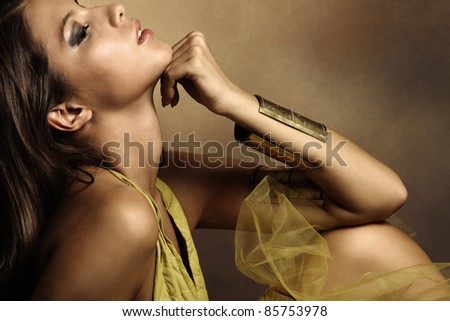 young beautiful woman portrait in golden tones, profile, small amount of grain added, studio shot - stock photo