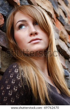 Young beautiful woman portrait on a brick wall