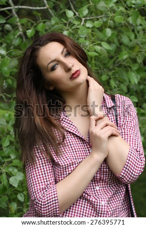 Young beautiful woman portrait on green background, spring tree - stock photo