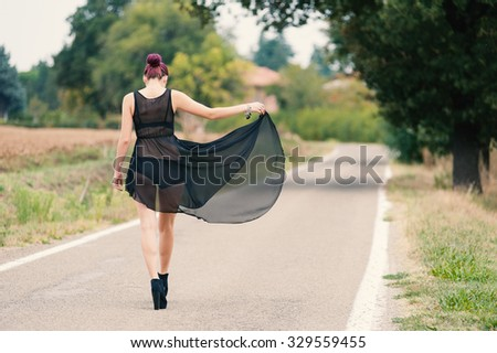 Young beautiful woman portrait walking on country road. Filtered image.