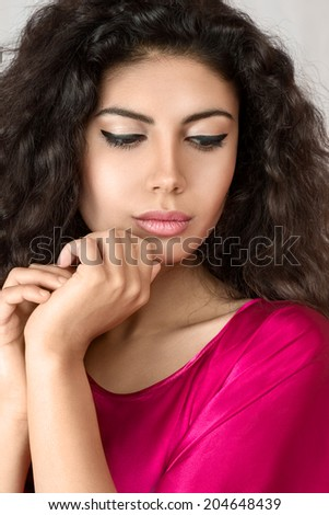 Young beautiful woman portrait with long curly hair posing in studio - stock photo