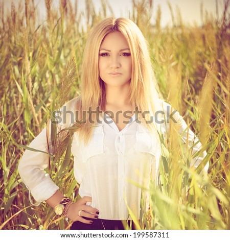 young beautiful woman poses in green thickets, looks in the camera. fashion model. Photo with instagram style filters - stock photo