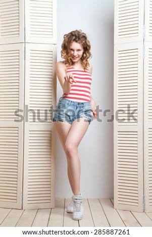 Young beautiful woman posing in front of a jalousie - stock photo