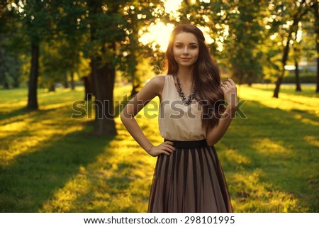Young beautiful woman posing in park at sunset. Outdoor summer portrait. Pretty stylish girl with long curly hair - stock photo