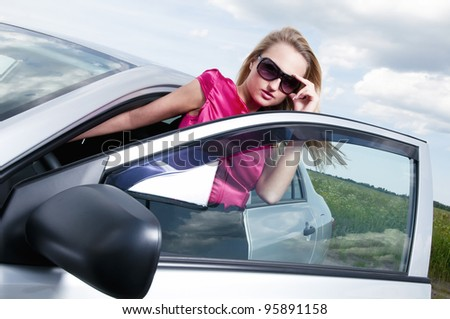 Young beautiful woman posing near the car - stock photo