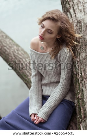 Young beautiful woman posing on a tree. Glamour fashion portrait. Autumn park. - stock photo