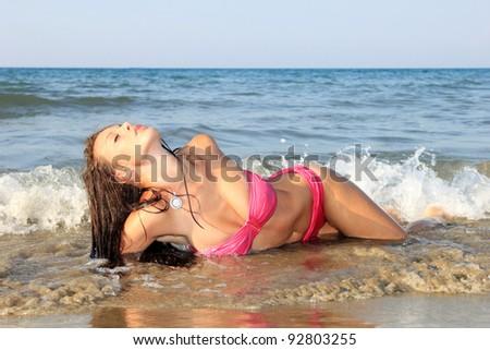 Young beautiful woman posing on the beach - stock photo