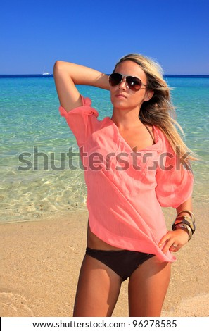 Young beautiful woman posing on the beach in the summertime - stock photo