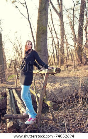 Young beautiful woman posing on the thin foot bridge across the river in spring - stock photo