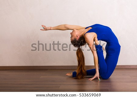 Young beautiful woman practicing yoga at home