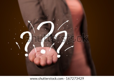 Young beautiful woman presenting hand drawn question marks - stock photo