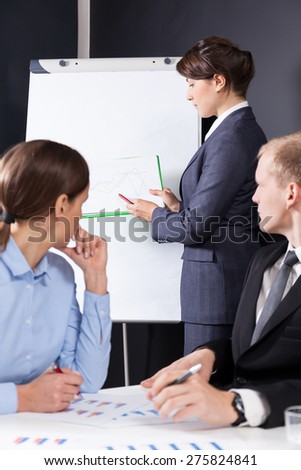 Young beautiful woman presenting her idea on a paper board