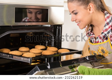 Young beautiful woman pulls cookies from the oven. - stock photo