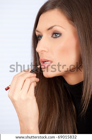 young beautiful woman putting on lip liner - stock photo