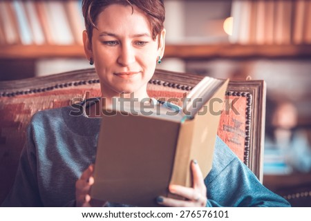 Young beautiful woman reading a book. Toned picture - stock photo