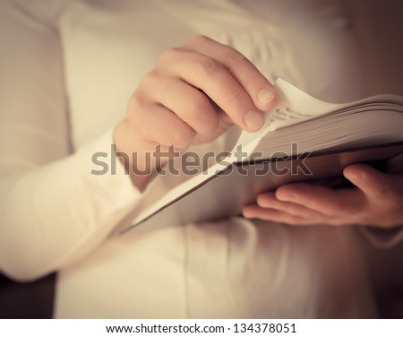 Young beautiful woman reading a interesting book - stock photo