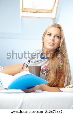 Young beautiful woman reading book  in bed - stock photo