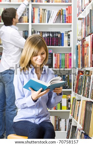 Young beautiful woman reading in the library - stock photo