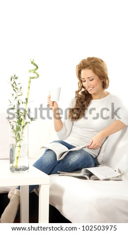 Young beautiful woman reading magazine on the sofa - stock photo