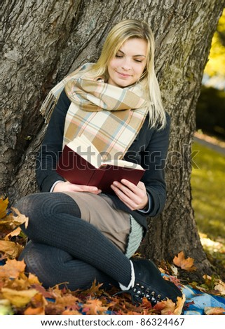 Young beautiful woman reading the book in at autumn park - stock photo