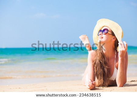 young beautiful woman relaxing at sunny tropical beach - stock photo