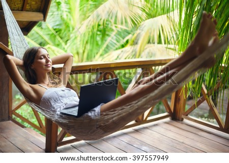 Young beautiful woman relaxing in a hammock with laptop in a tropical resort. Break time - stock photo