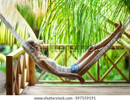 Young beautiful woman relaxing in hammock in a tropical resort - stock photo
