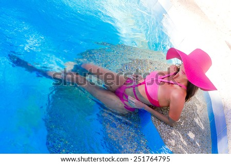 young beautiful woman relaxing in pool, summer vacations in tropics - stock photo
