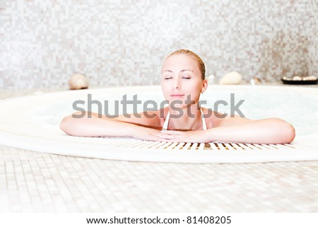 Young beautiful woman relaxing in the Jacuzzi - stock photo