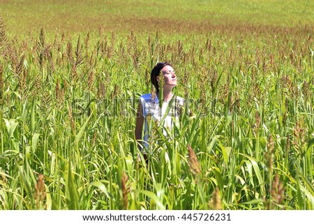 Young beautiful woman relaxing in the middle of a green cereals field during the last days of summer in the Pyrenees mountains - stock photo